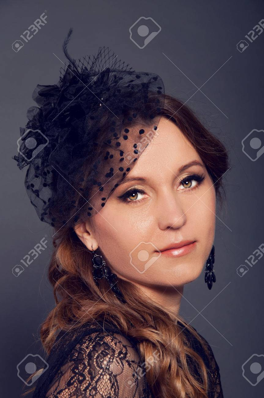 e7d27a6df2c57 Elegant young woman in black lace dress and black veil hat with long curly  hair.