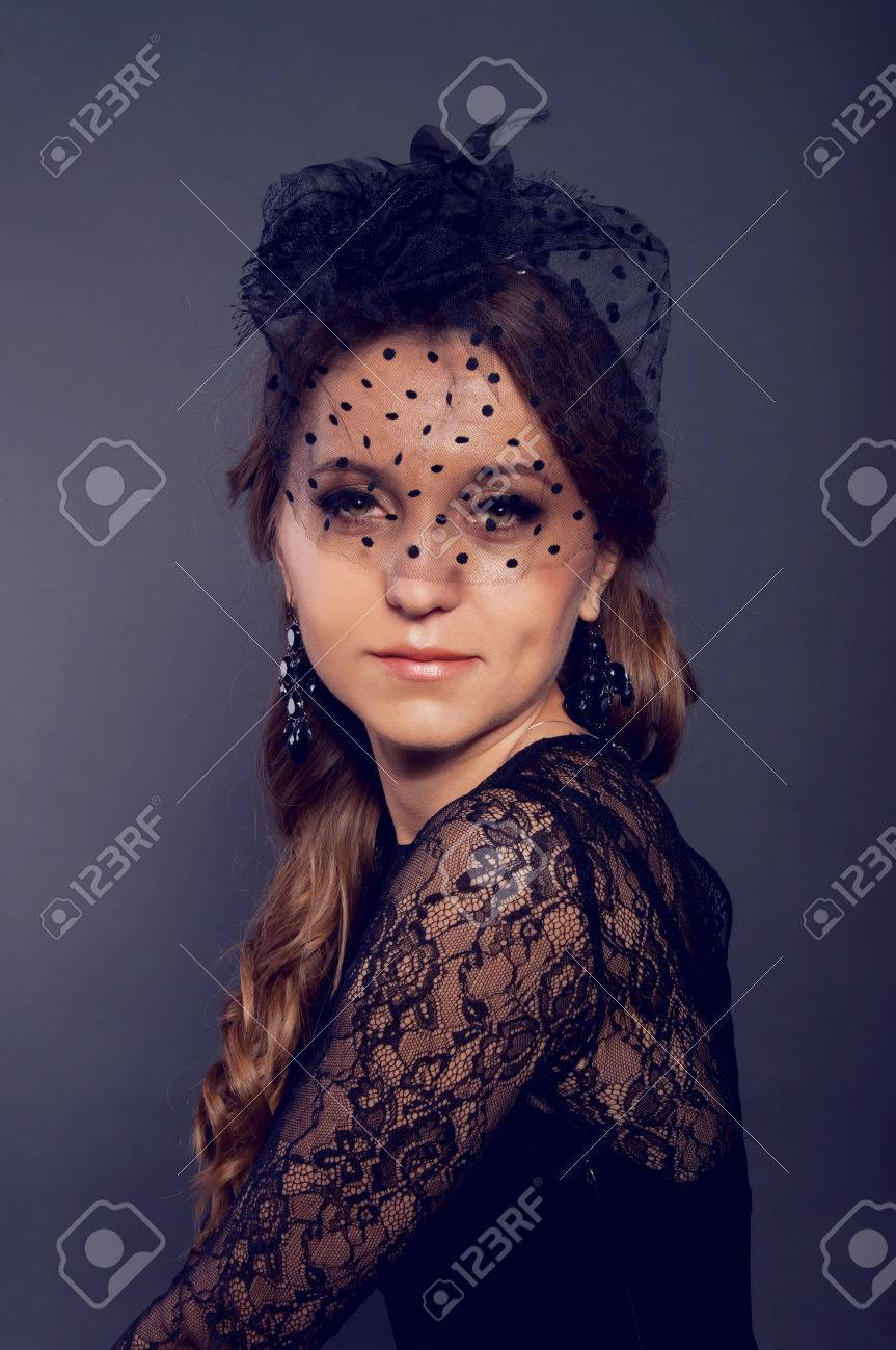 Elegant young woman in black lace dress and black veil hat with long curly  hair. 013ea893343c