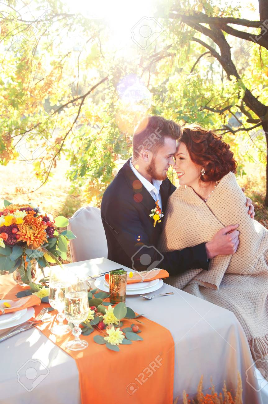 Bride And Groom At The Wedding Table. Autumn Outdoor Setting. Romantic  Scene. Stock