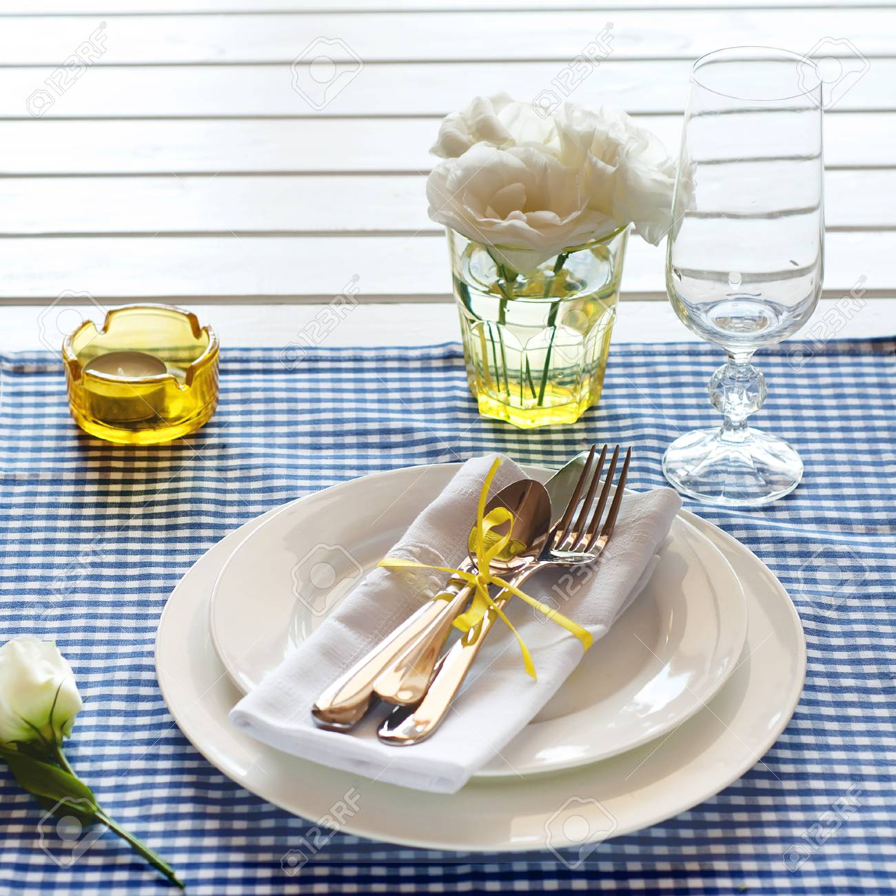 Stock Photo   Table Setting With Blue Checkered Tablecloth, White Napkin,  Silverware, Yellow Decoration And Flowers