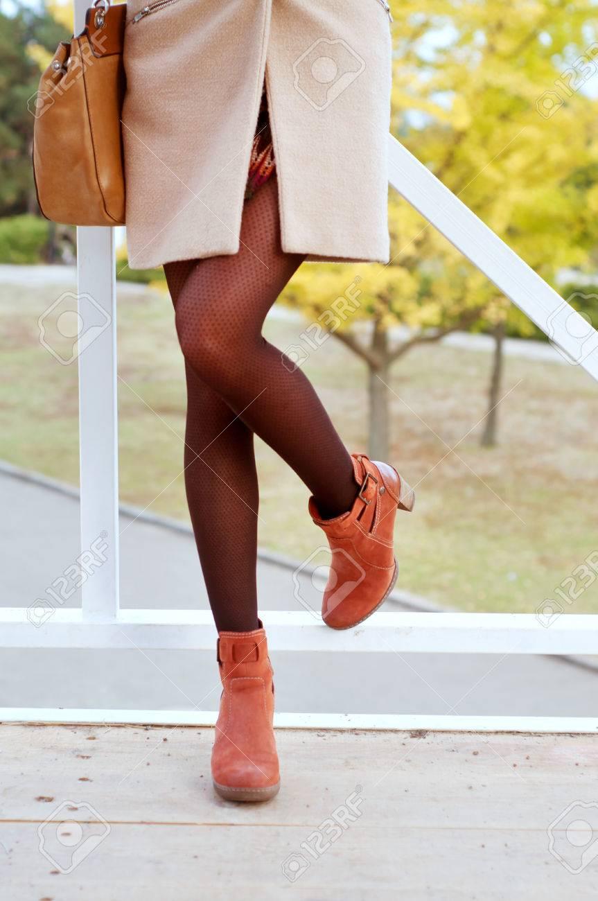 mieux aimé 80ceb cd0b2 Femme portant des collants noirs et des bottes en daim orange vêtus de  manteau beige et mini jupe. Automne mode;