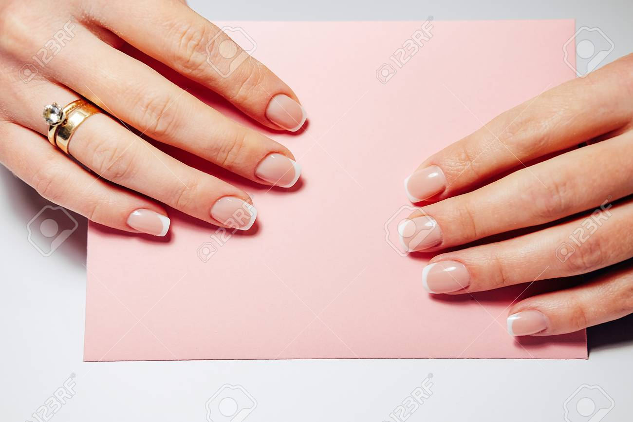 French Nail Extensions Women With Beautiful Manicure And Wedding Ring Holding A Pink Envelope