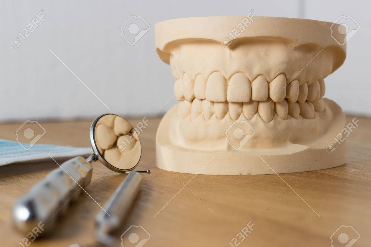 Dental mold of a set of false teeth with dental tools on a wooden