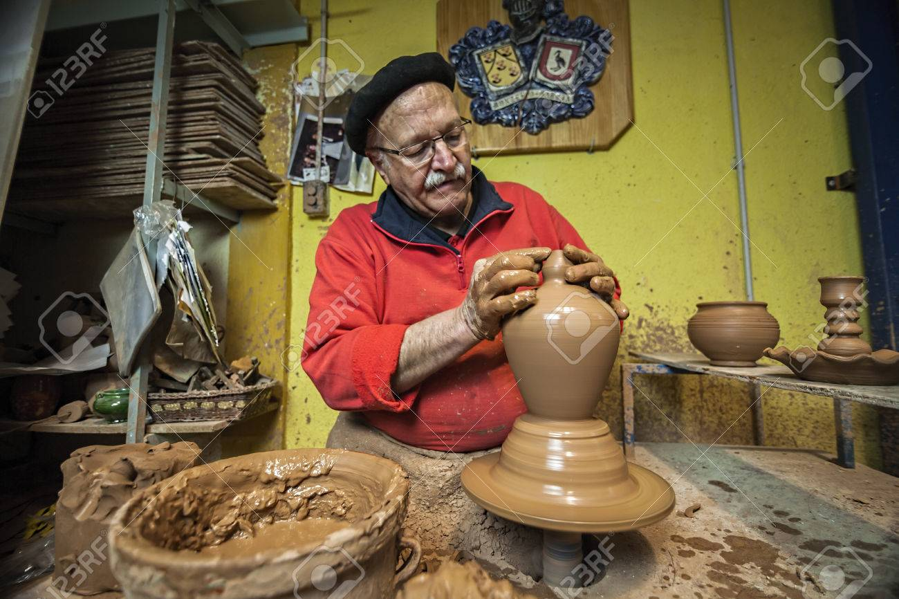 Potter making a water jug in classic mud, clay pottery ceramics