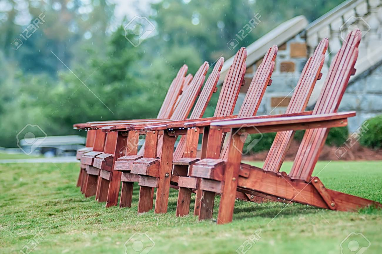 two wooden adirondack chairs on lush green lawn stock photo picture