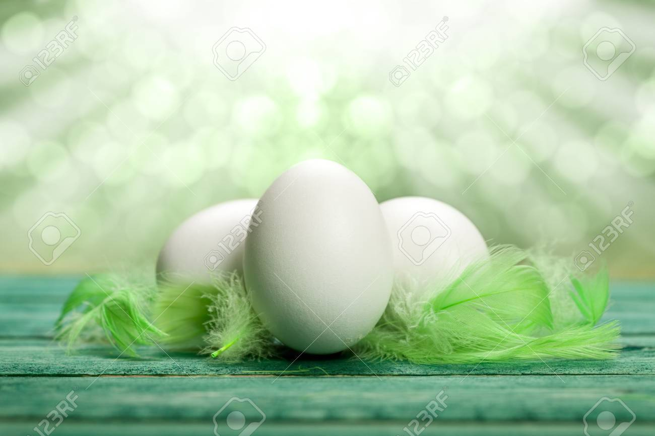 Three white eggs and green plumes Stock Photo - 10527427