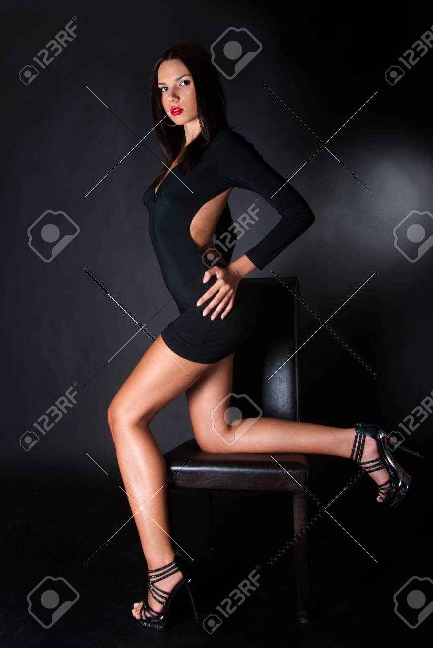 Stock Photo - woman with sexy body and sexy poses wearing black dress on  black background