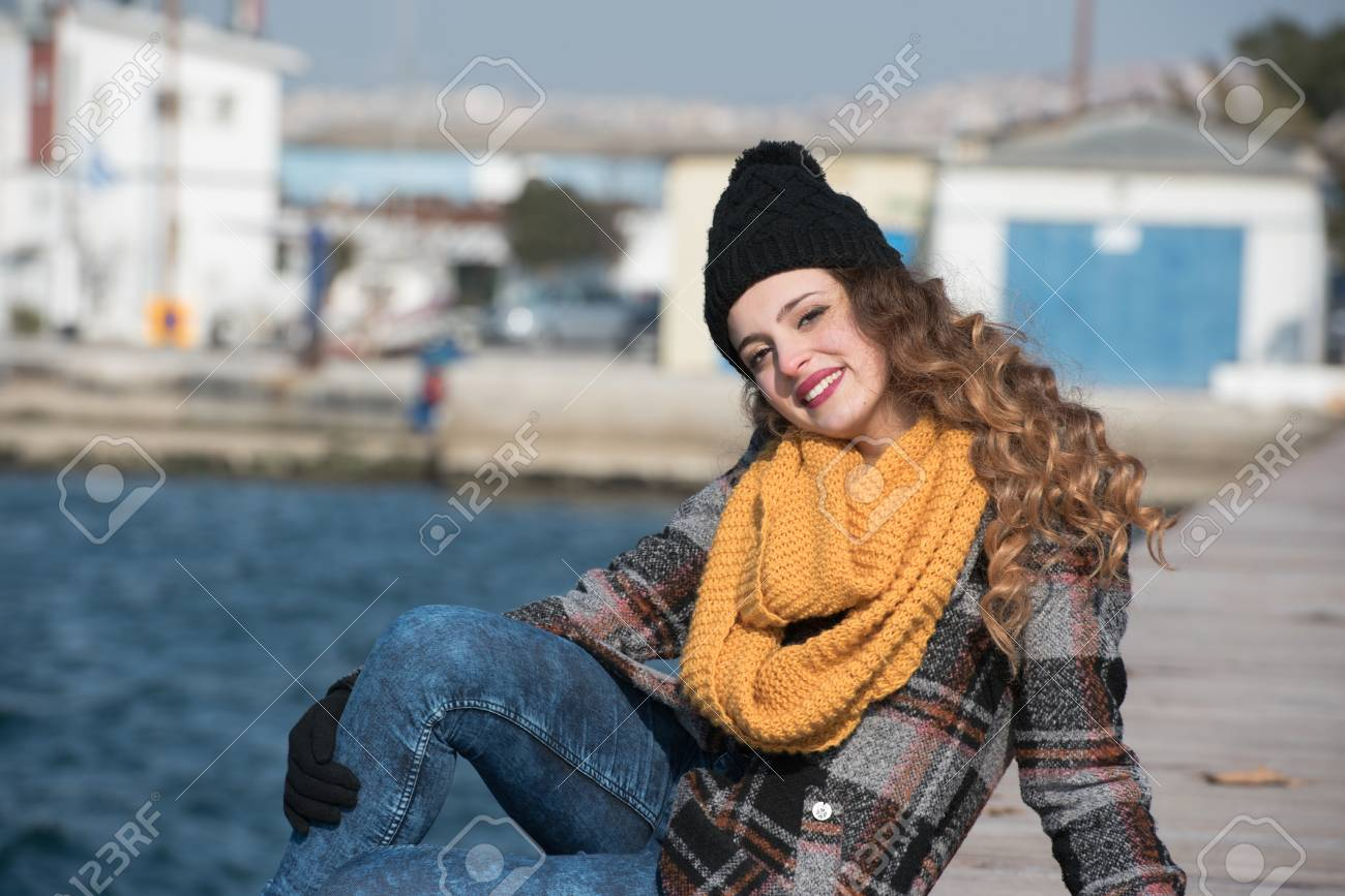 Stock Photo - Sweet curly teen sitting on the edge of the port wear scarf  and skull cap f9ee5e0ac50