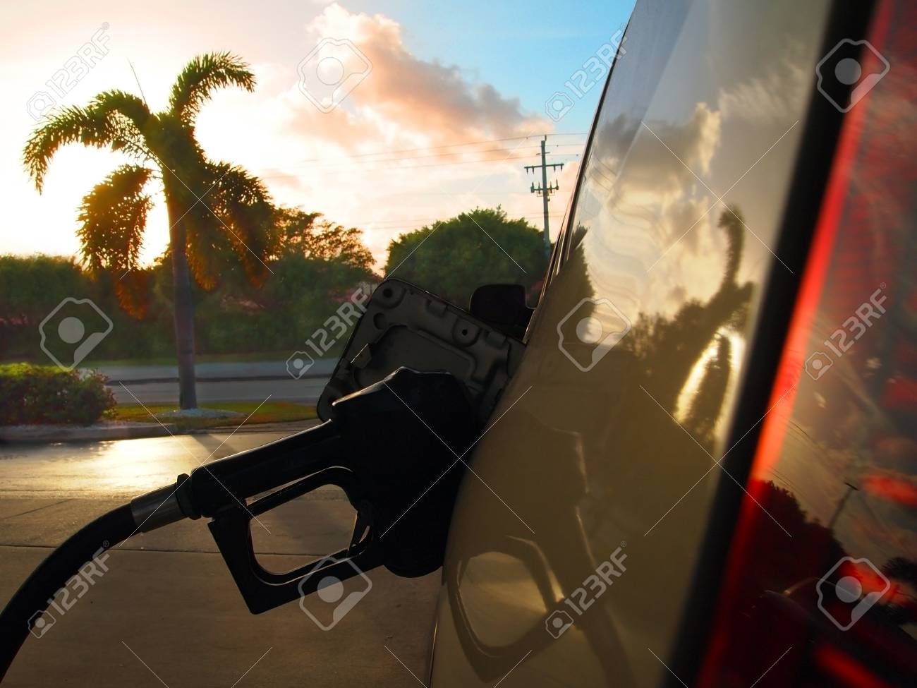 Close up on gas pump, filling the tank of an automobile at sunset with palm tree and colorful clouds in the background Stock Photo - 17195878