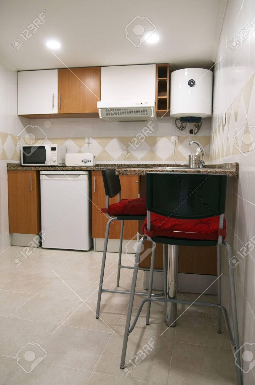 Actualizado cocina pequeña. Contador con sillas altas. Armarios, pequeña  nevera, horno microondas, extractor de humos y calentador de agua.