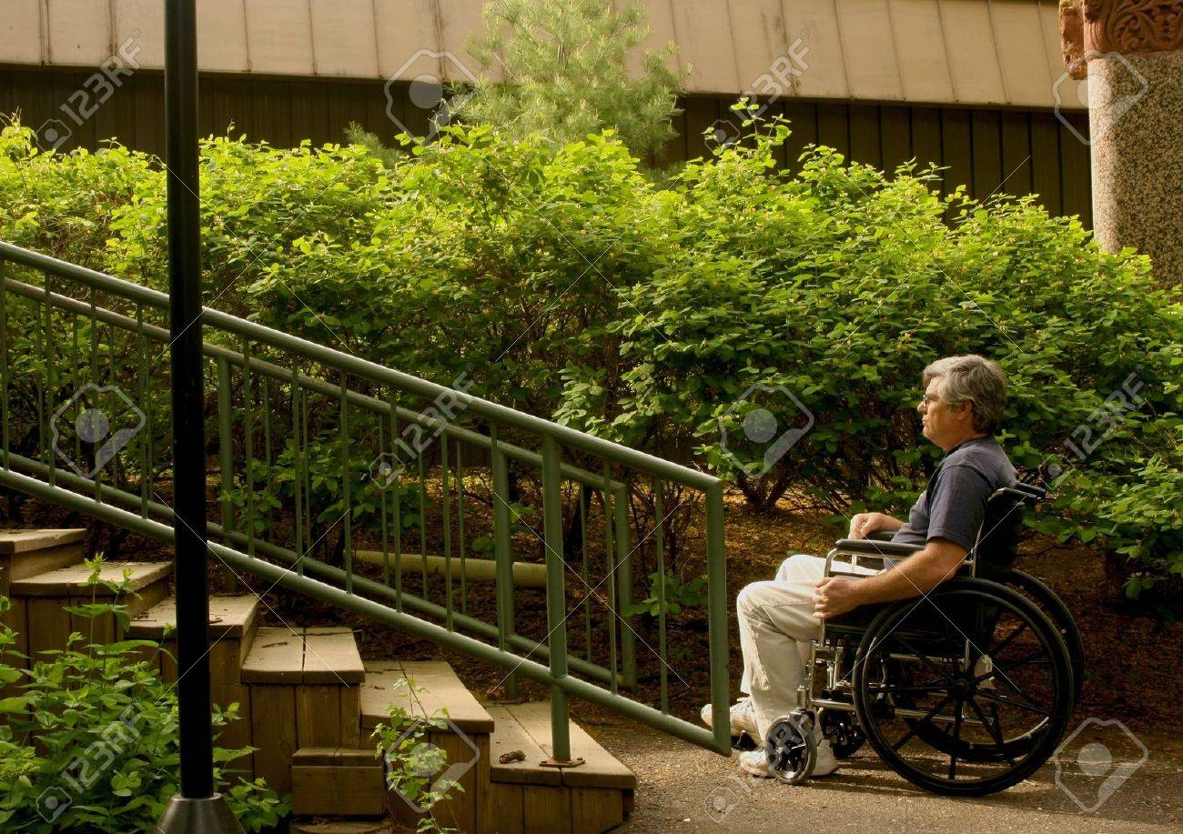 man sitting in a wheelchair contemplating a set of stairs Stock Photo - 4931714