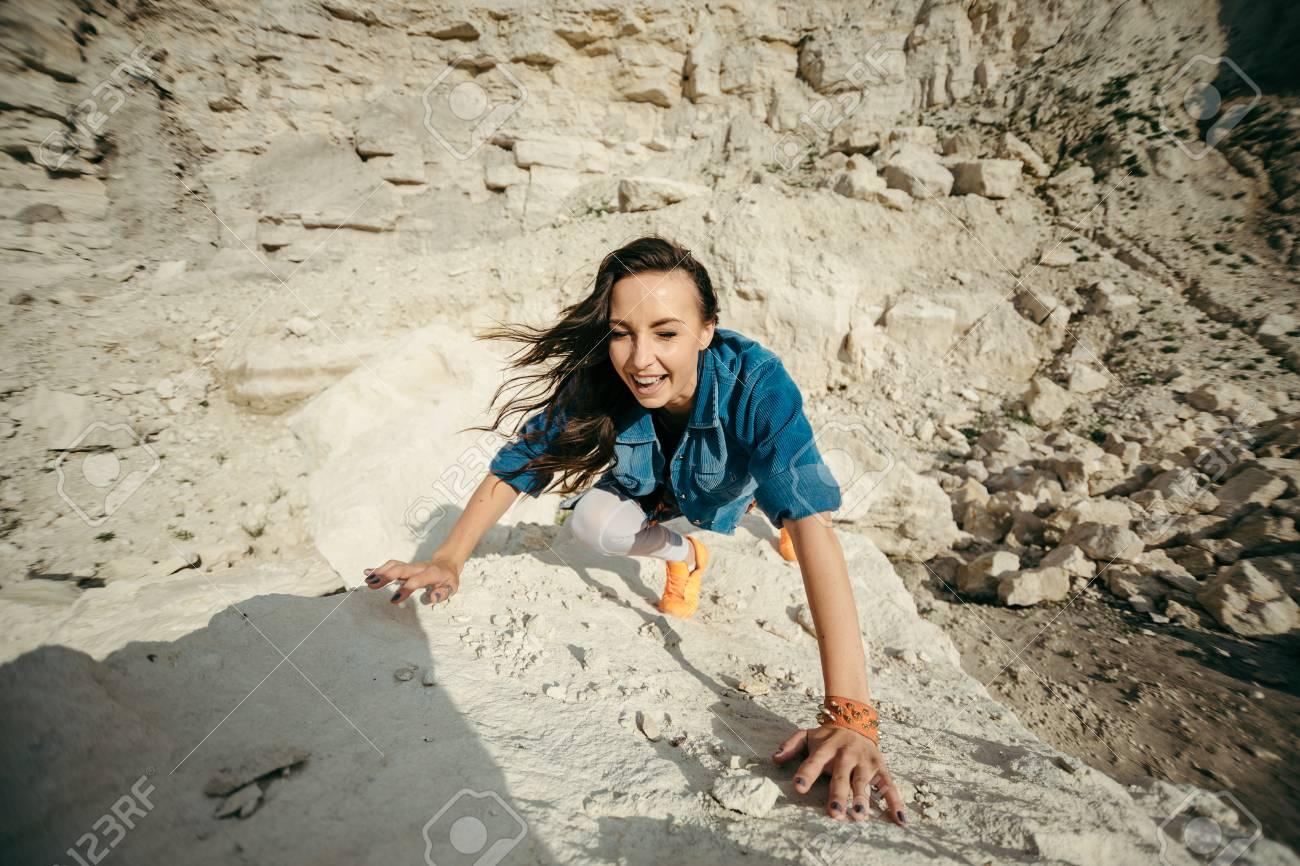 Foto de archivo - La mujer joven que presenta y que baila cerca de las  montañas hermosas vistió la ropa colorida 3b9aa587b82