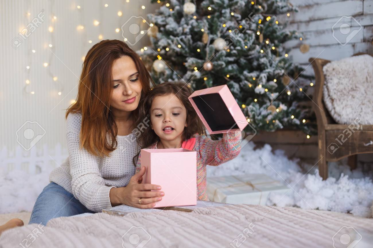 Happy Mom With Kid Looking Inside Of Christmas Gift Box. Happy ...