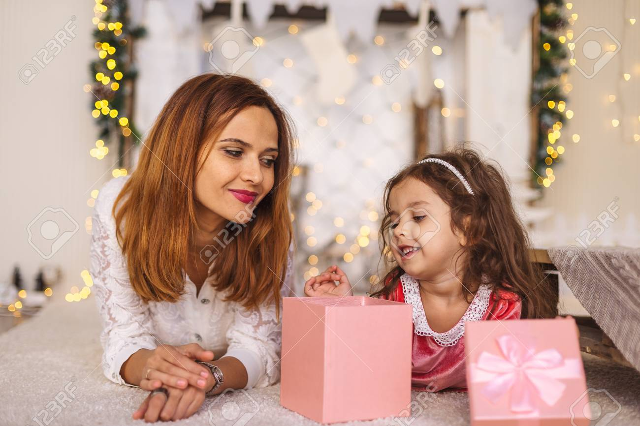 happy mom looking to her kid while she looks inside christmas gift box happy toddler