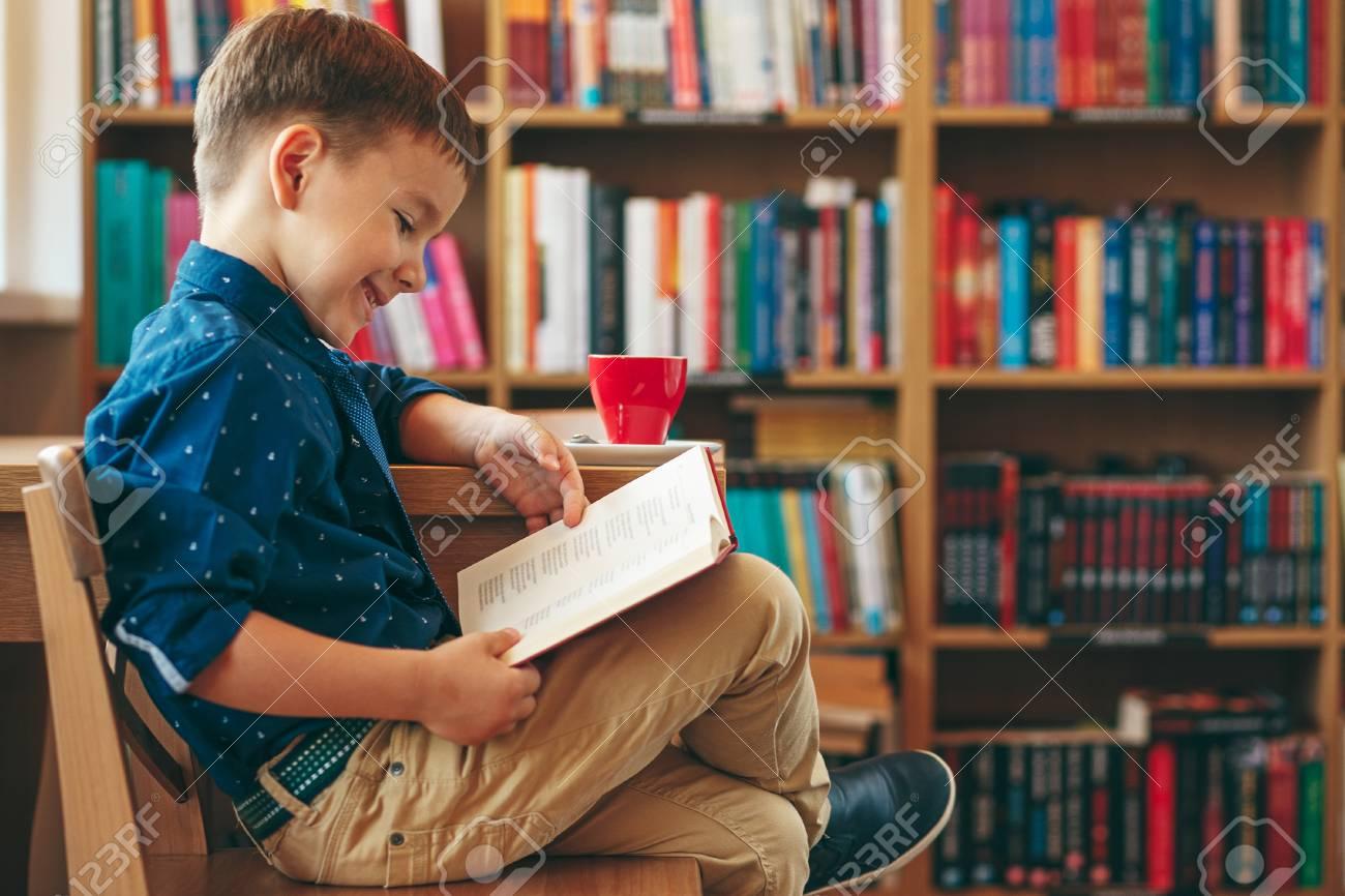 Immagini Stock Ragazzo Che Legge Un Libro Seduto Su Una Sedia Vicino A Un Tavolo Con Una Tazza Di Te Sullo Sfondo Del Multi Scaffale Colorato In Biblioteca Istruzione Conoscenza Preparazione