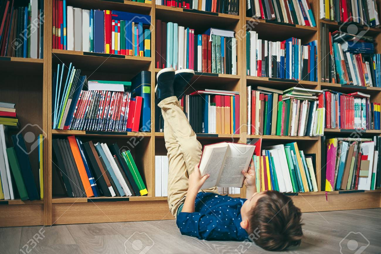 Boy Laying On The Floor With Feet Up Reading A Book Against Multi Colored