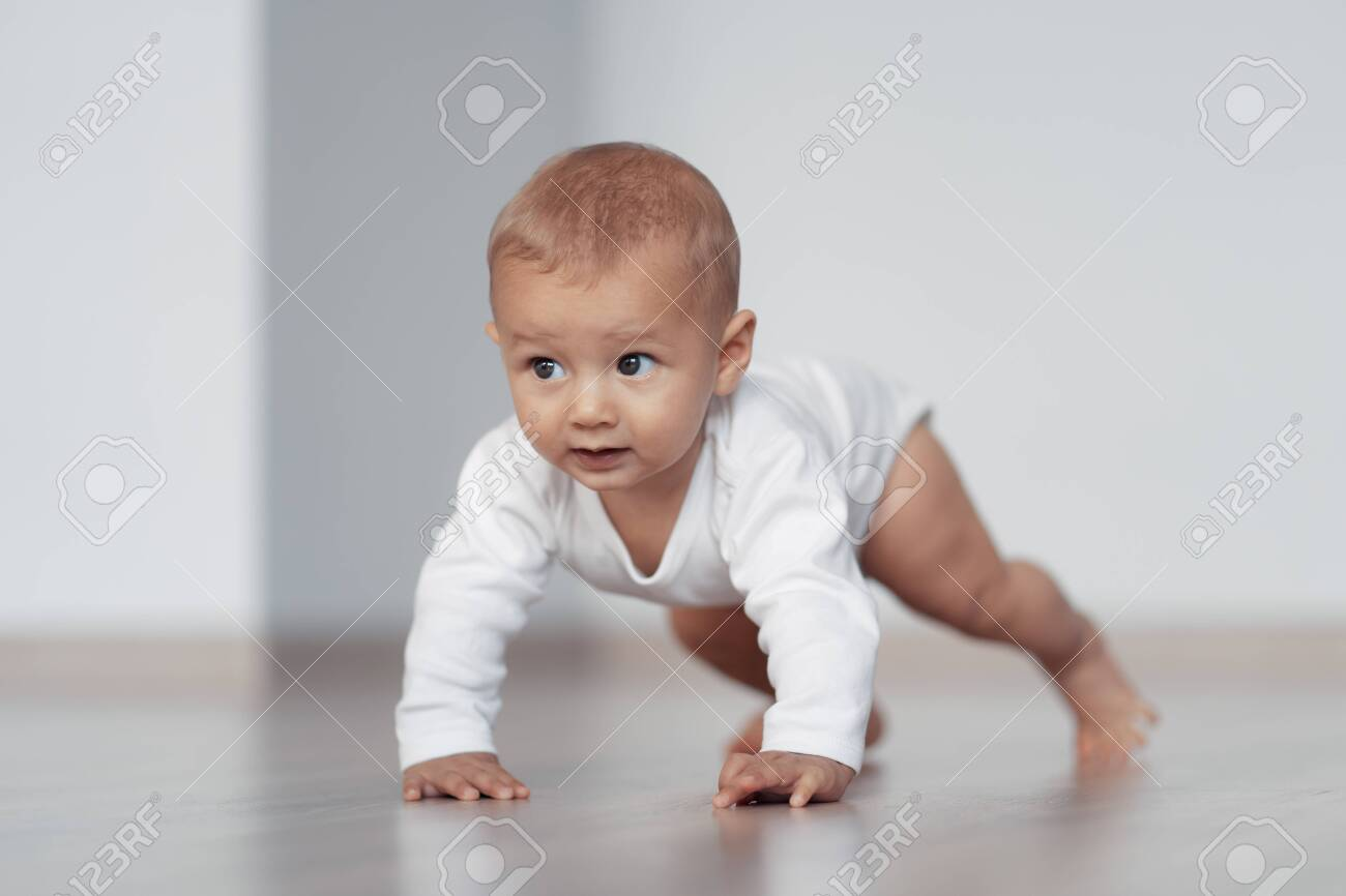 The kid is trying to take his first steps - 144531886