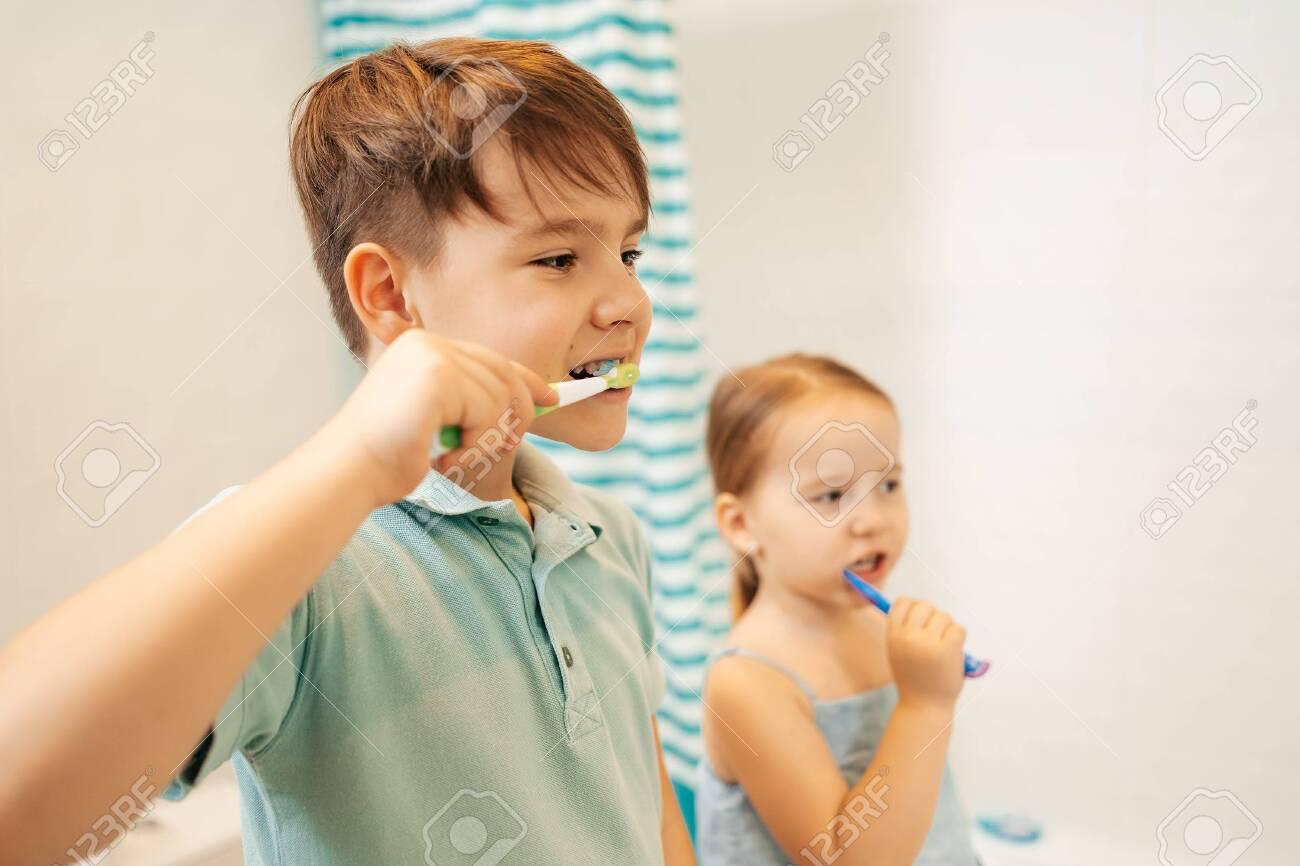 Indoor portrait of cute kids brushing their teeth in the bathroom, happy family and dental hygiene - 151764429