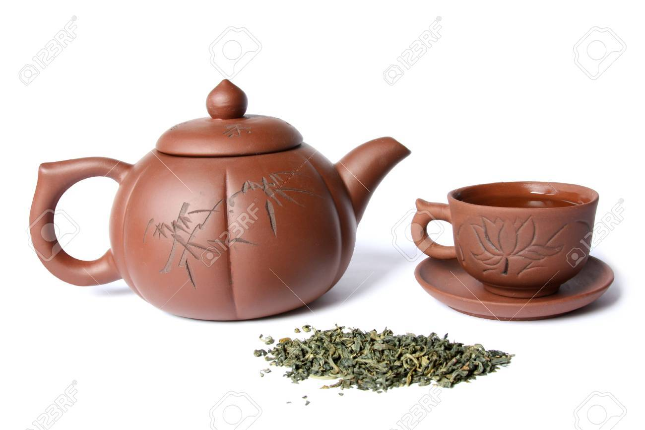 Teapot, teacup and a pile of green tea. Isolated on white - 5771357