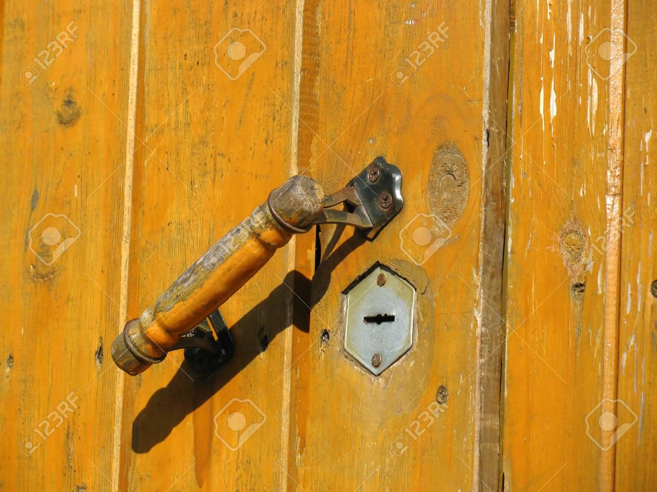 Old wooden weathered door with doorhandle and keyhole Stock Photo - 7195473