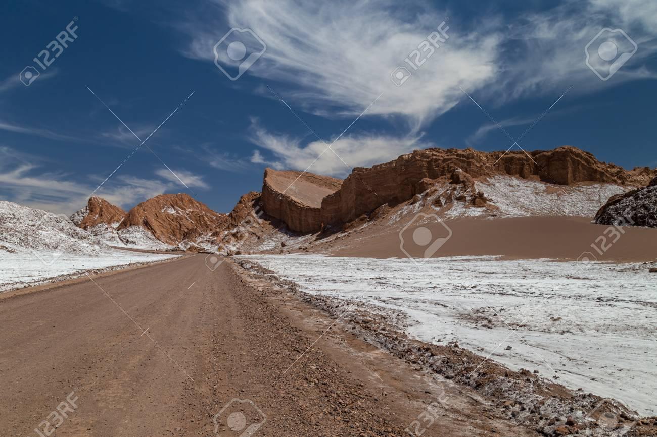 Road crossing Valle de la Luna. Dunes and rock formations covered with salt. Atacama, Chile - 115409165