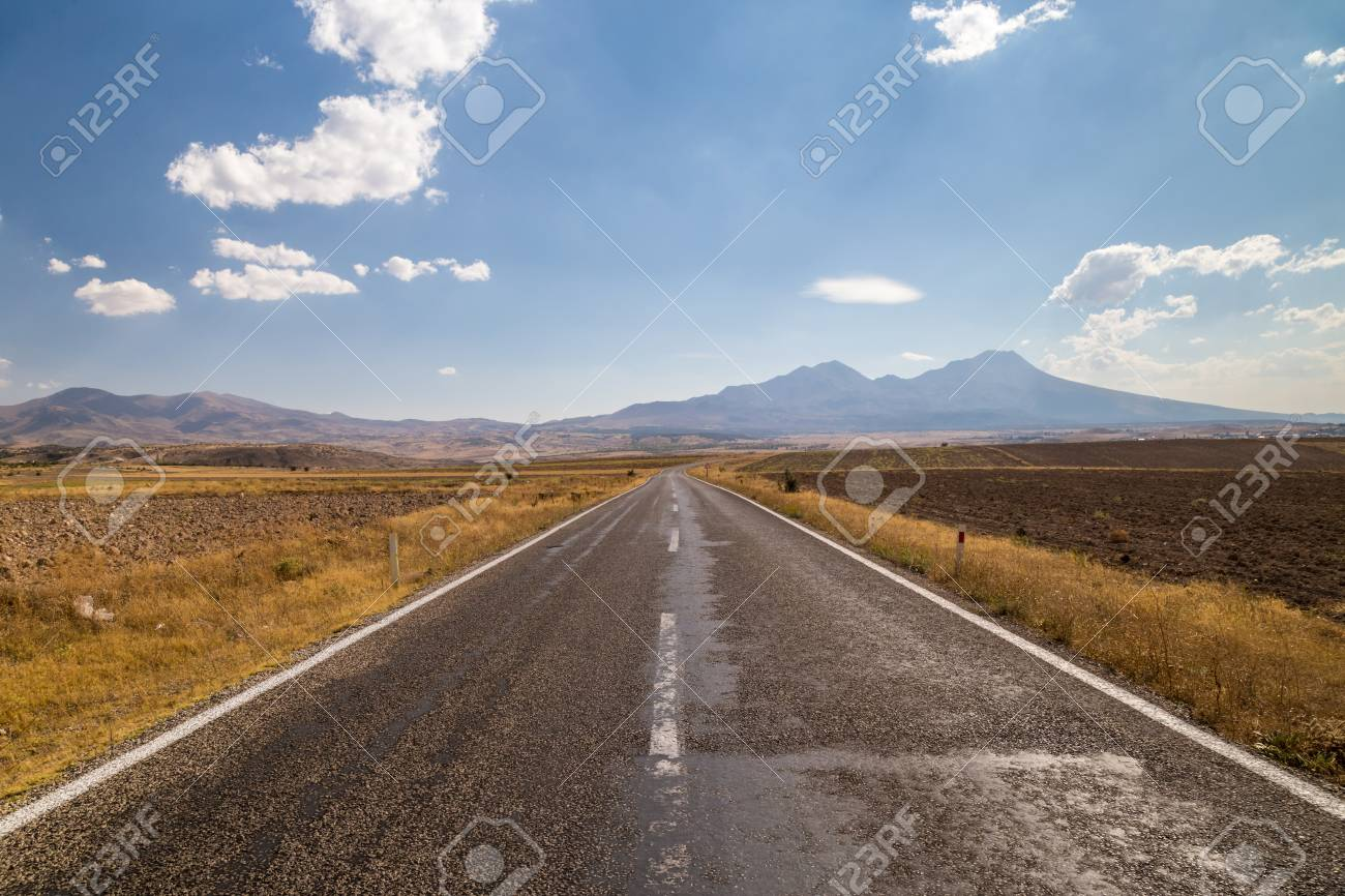 Long straight road going across countryside, leading to mountains far away - 115409167