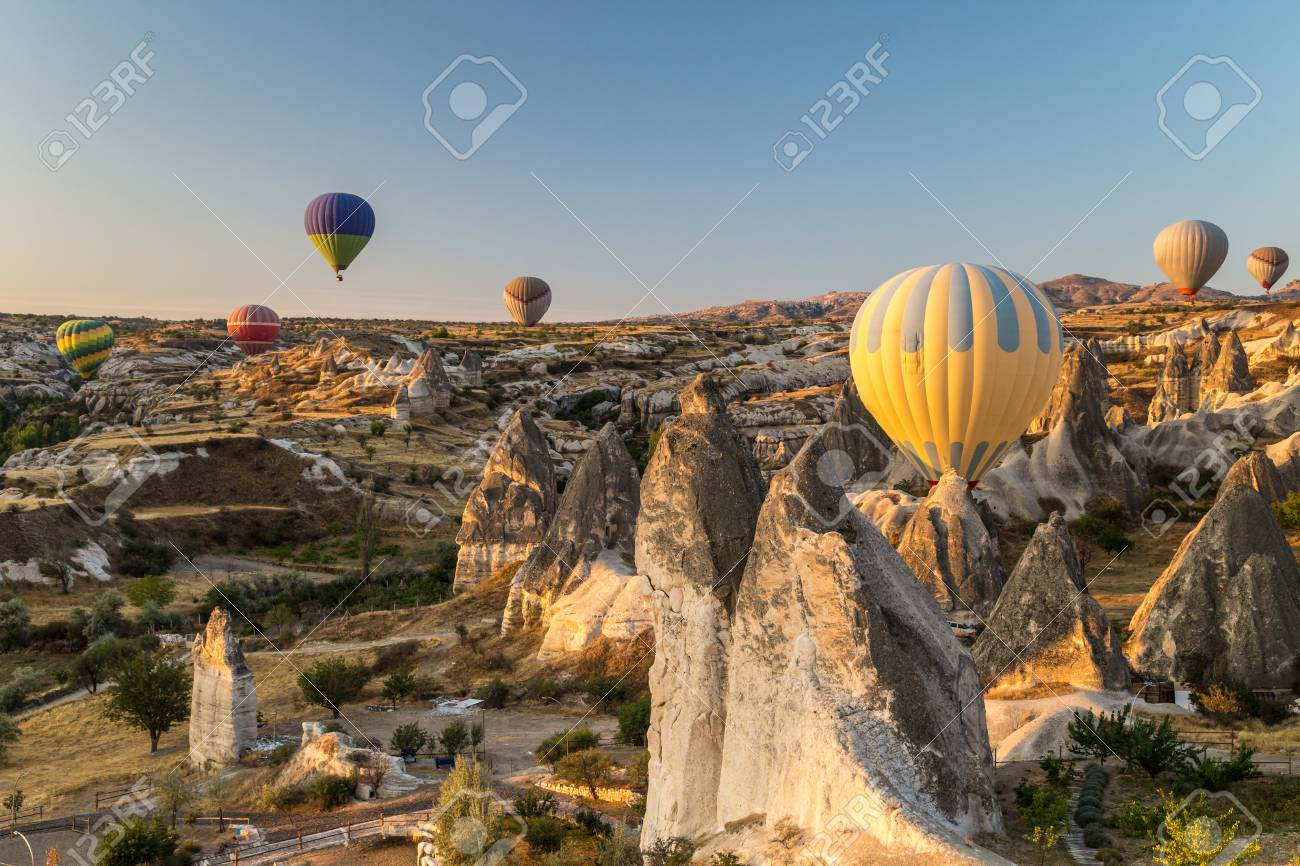 Hot air balloons flying at sunrise over rock formations in Cappadocia, Turkey - 115409420