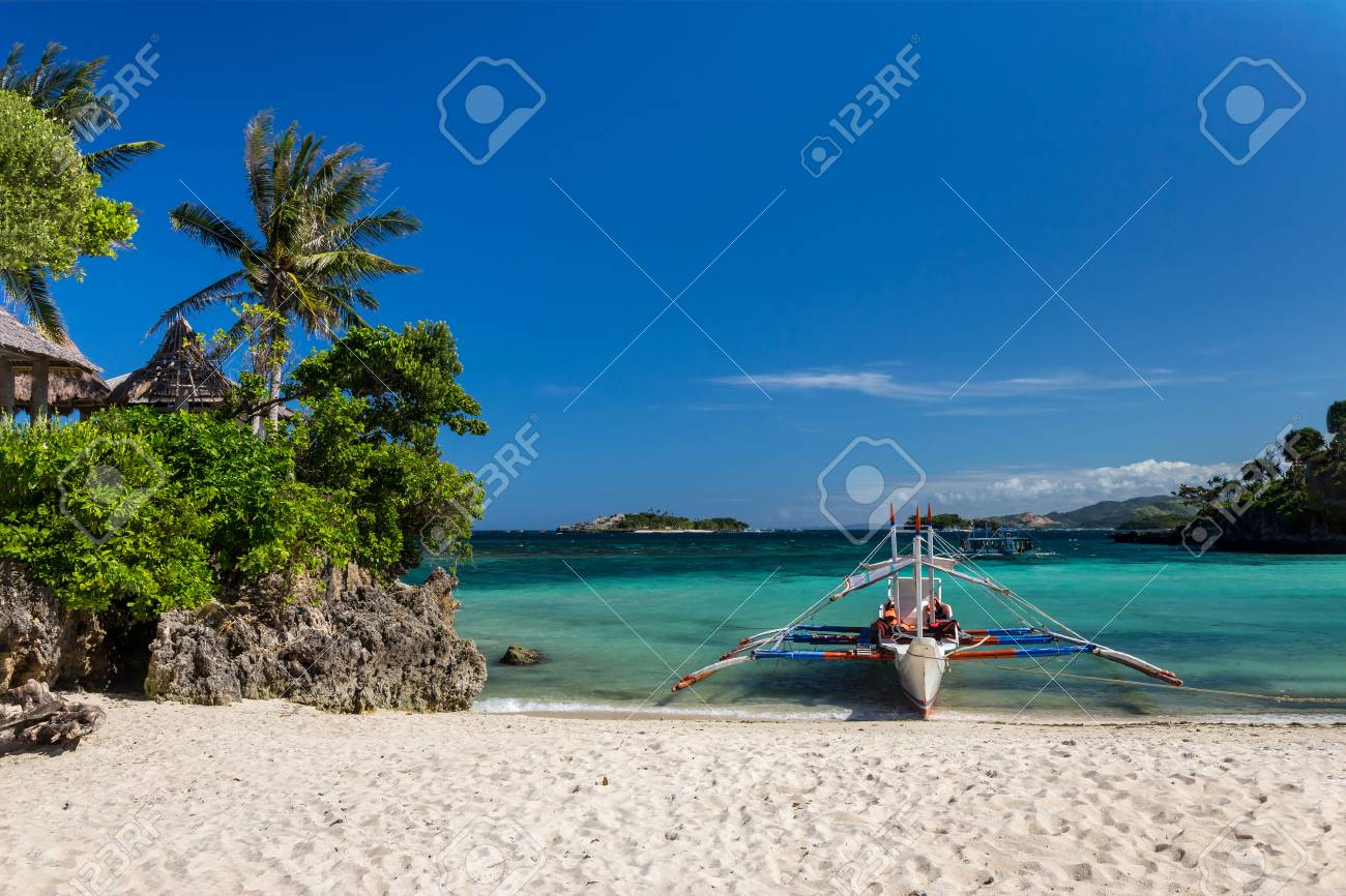 Traditional Philippine double-outrigger boat, known as bangka, banca and paraw, at a pristine white sand beach - 115409478