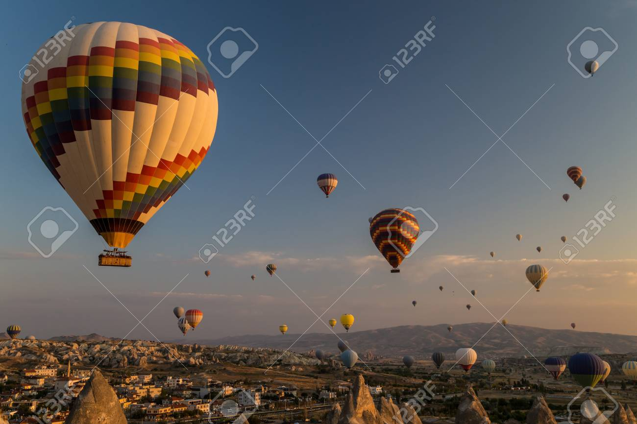 Hot air balloons flying at sunrise over rock formations in Cappadocia, Turkey - 115409789