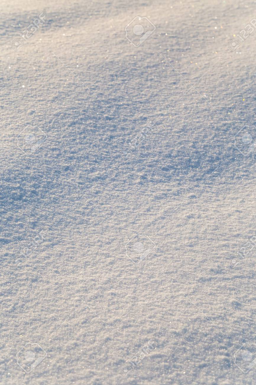 Background of white snow sparkling in the sun. Shallow depth of field - 115410102