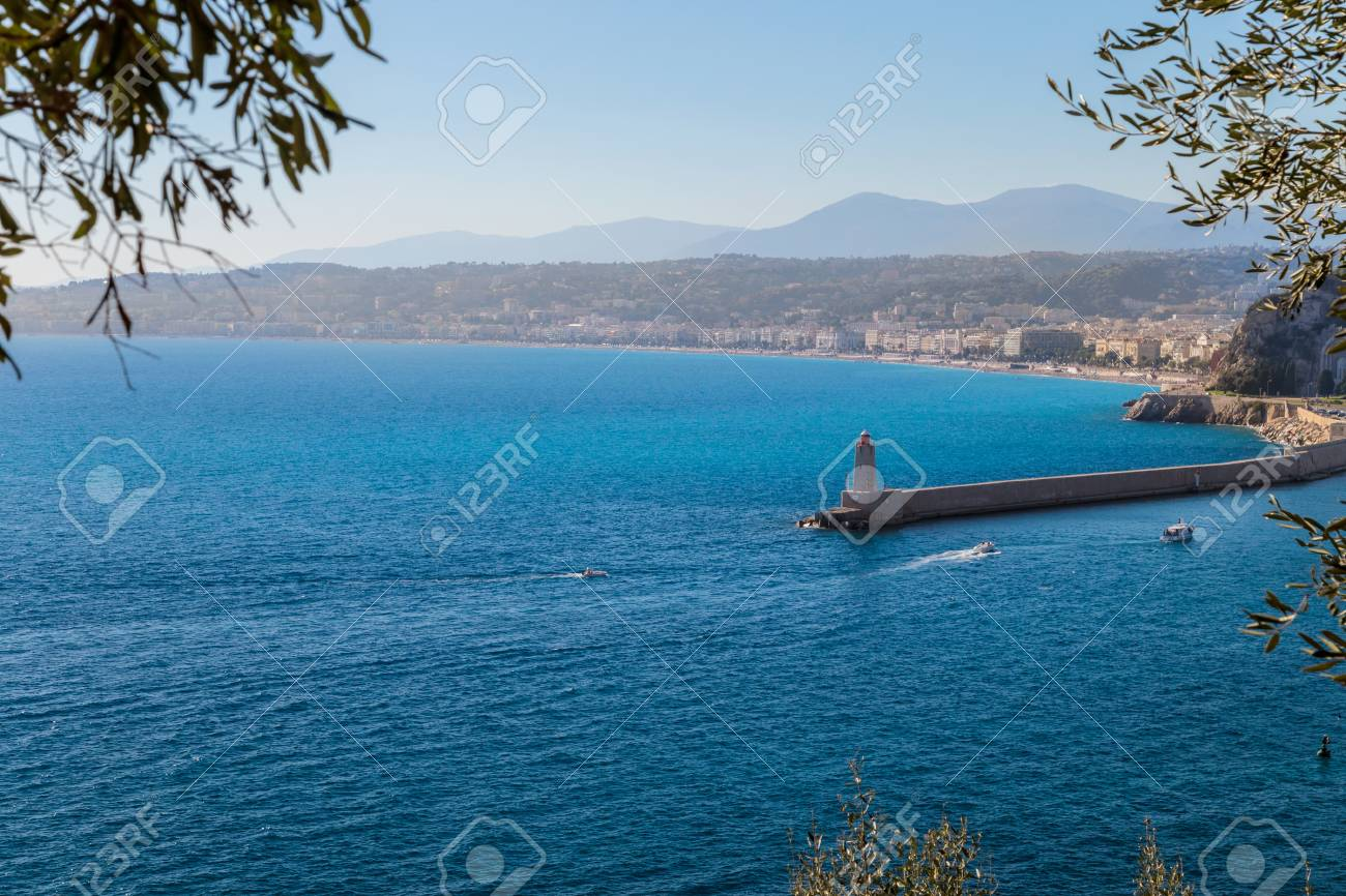 View to a lighhouse, a beach and a city. Nice, French Riviera - 115410315