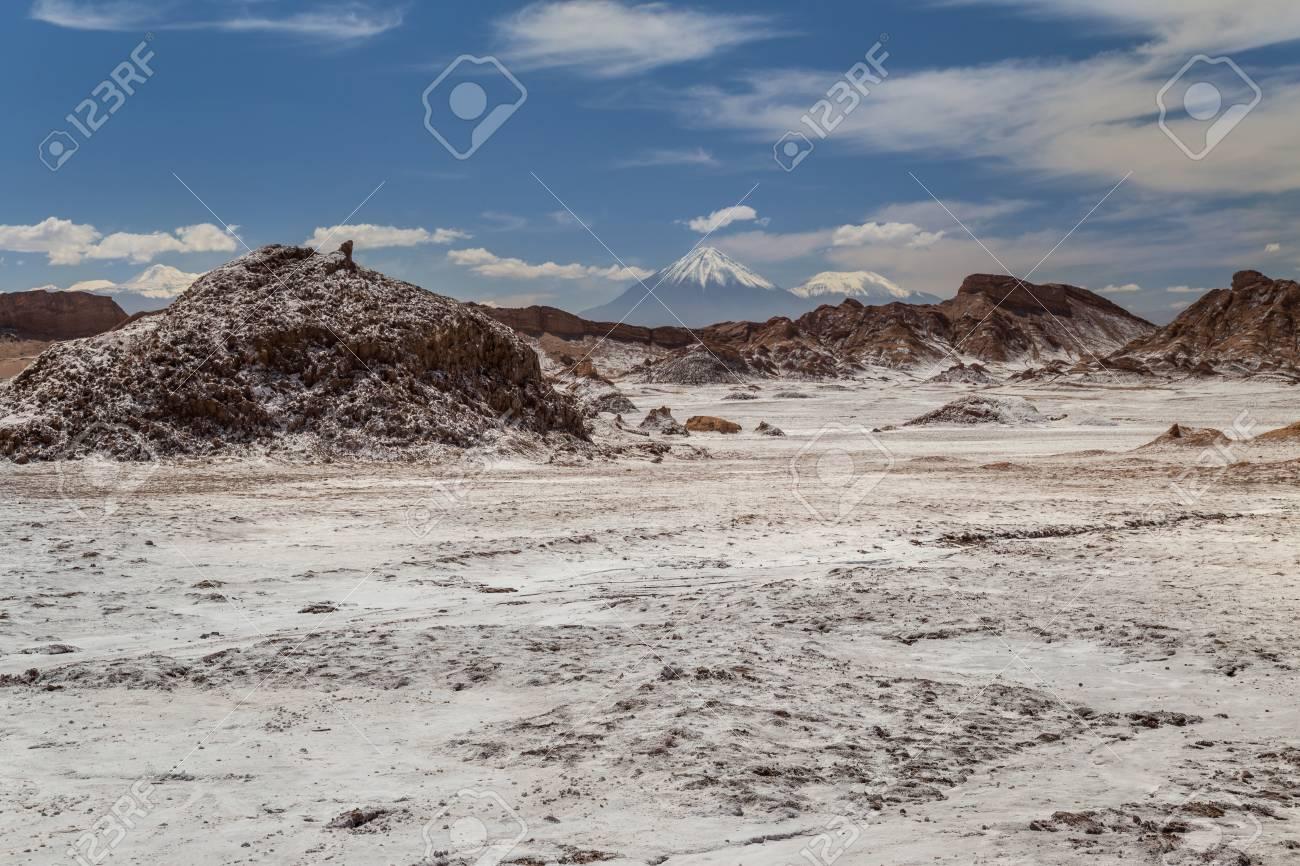 Rock formations covered with salt, volacanos on the background. Valle de la Luna, Atacama, Chile - 115410320
