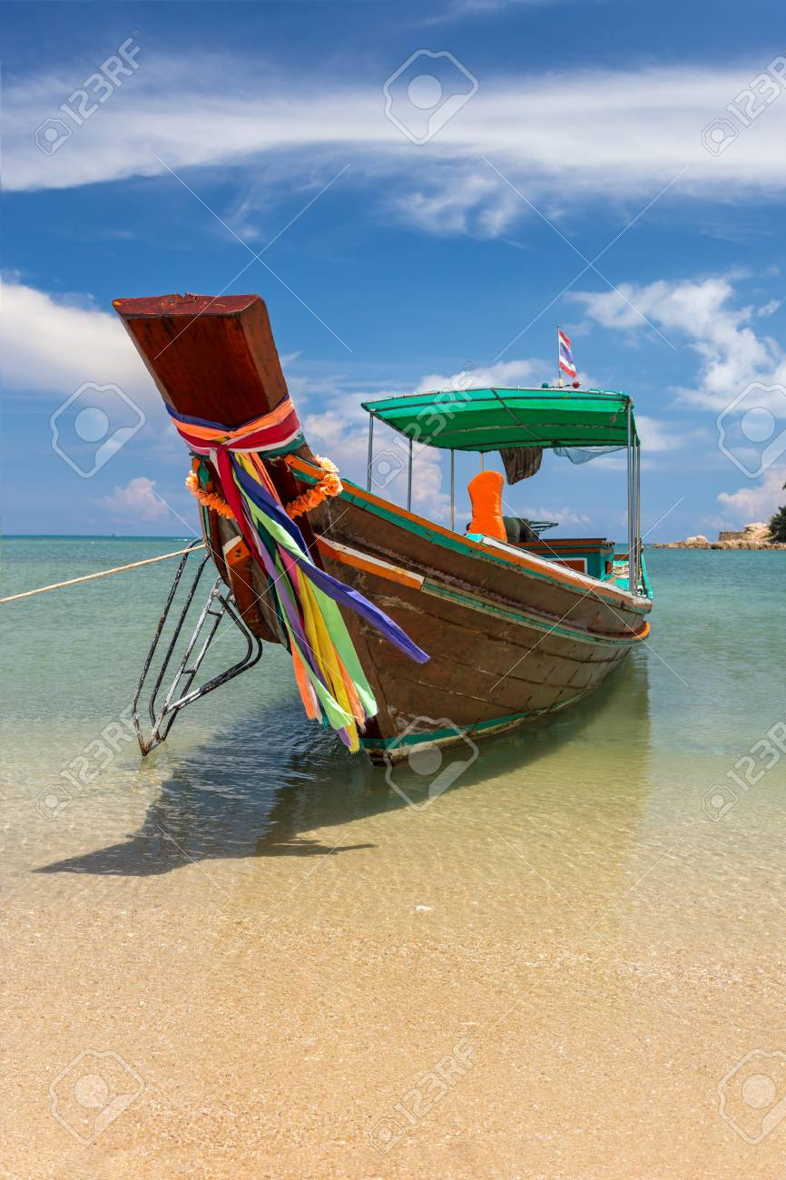 Traditional thai long boat moored at a beach - 115410332