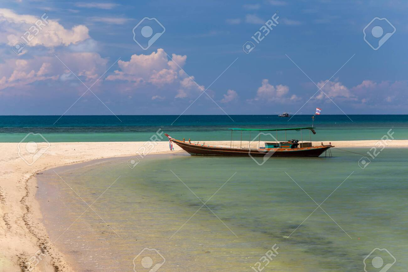 Traditional thai long boat moored at a beach - 127056872