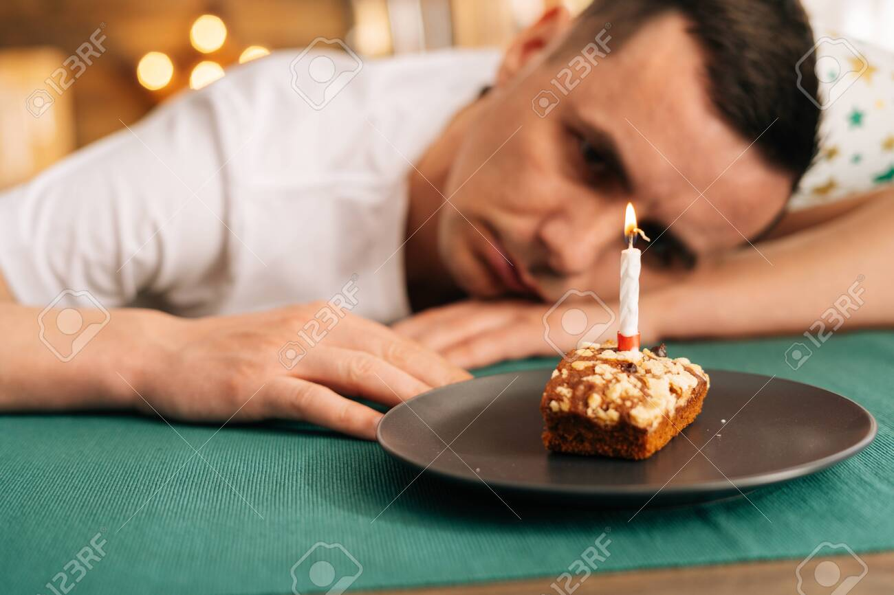 Awe Inspiring Sad Lonely Young Man In Festive Hat Celebrating Birthday Alone Funny Birthday Cards Online Sheoxdamsfinfo