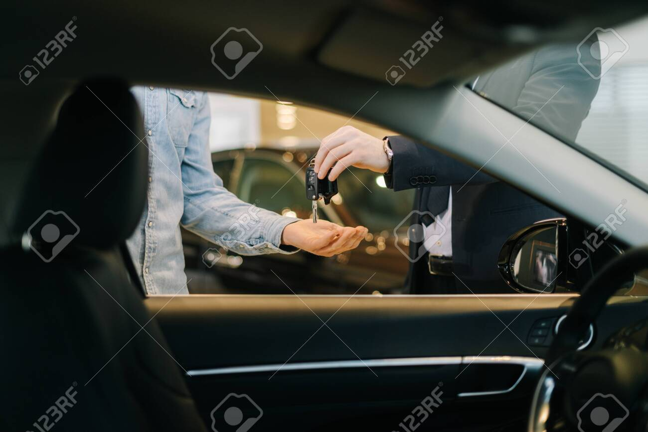 Close-up of car salesman handing over keys for new car to young man buyer in auto dealership, view from interior of car. Concept of choosing and buying new car at showroom. - 145644405