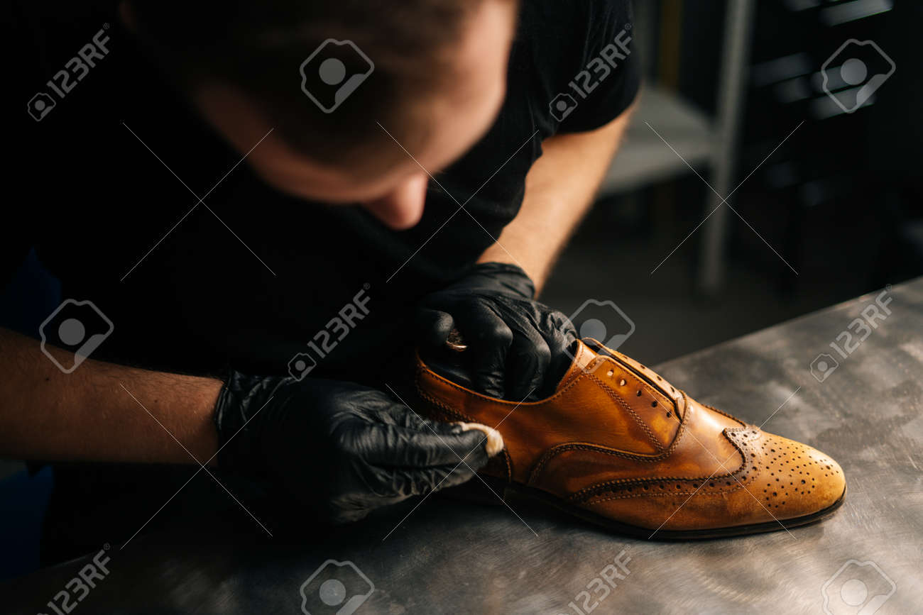 Top close-up view of professional shoemaker wearing black gloves polishing old light brown leather shoes. Concept of cobbler artisan repairing and restoration work in shoe repair shop. - 165816413