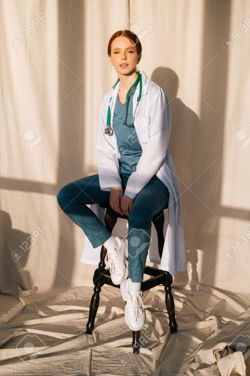Portrait of serious sensual female doctor in white coat sitting on chair near window in sunny day in medical clinic office. Young redhead woman surgeon posing with stethoscope looking at camera. - 169892799