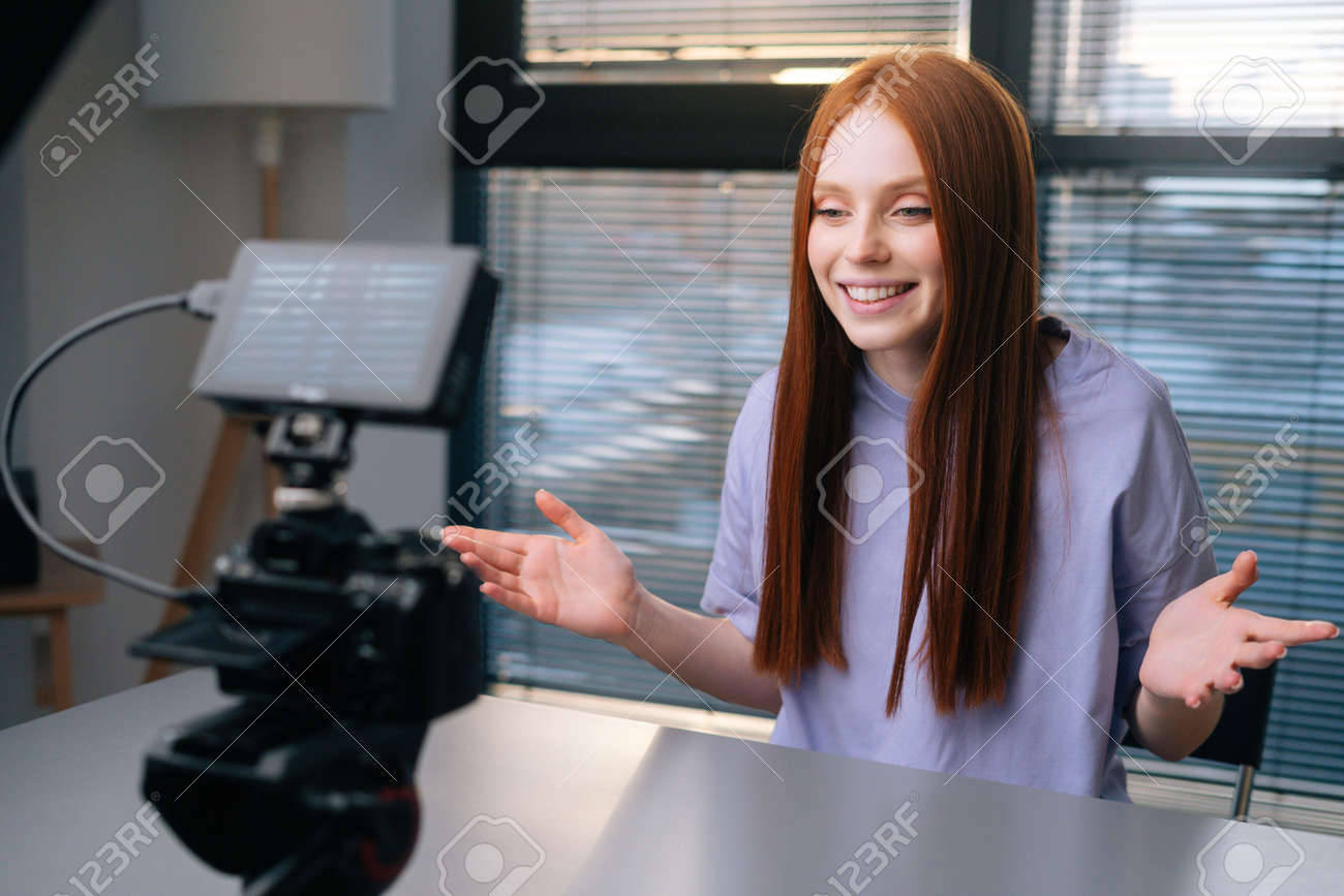 Side view of cheerful young woman blogger turns on camera, waving hand in greeting and starts talking looking into camera. Smiling redhead female record commercial online video course at home office. - 169892811