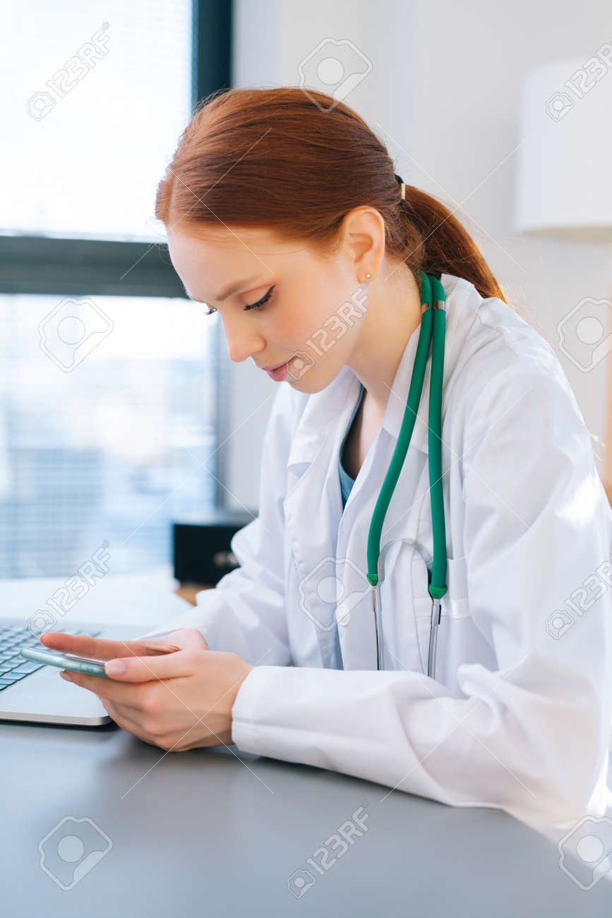 Close-up side view of positive female doctor in white coat typing message on phone, sitting at desk with laptop near window in sunny day. Focused woman physician giving remote diagnose to patient. - 169892814