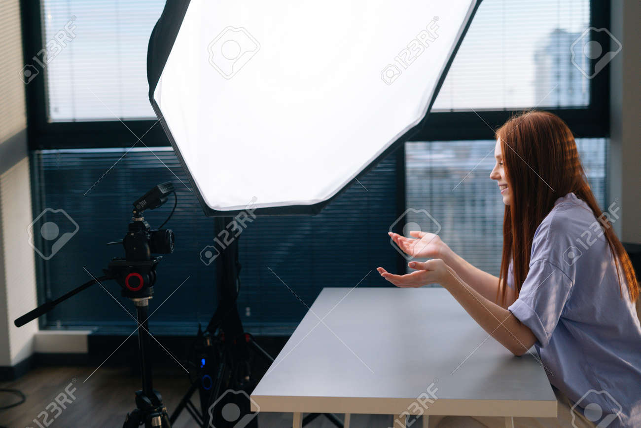Side view of successful young woman blogger recording video vlog using professional camera and softbox sitting at desk on background of window. Happy redhead female having online conference in office. - 169892822