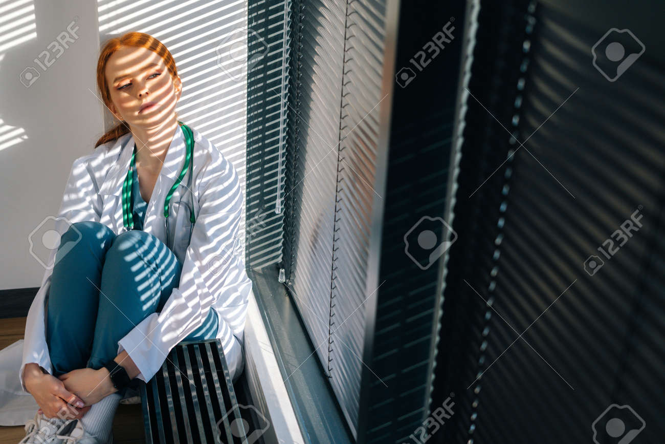 Close-up of depressed sad young female doctor in white coat sitting on floor hugging legs with hands near window. Unhappy woman physician depression feeling worried about professional malpractice. - 169892825
