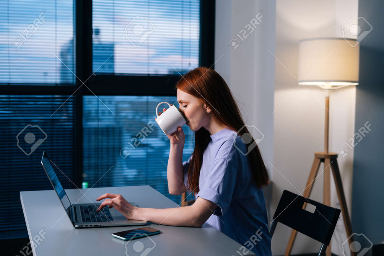 Cheerful redhead young business woman typing on laptop sitting at desk in dark office and drinking coffee from mug. Happy businesswoman working on computer sitting at desk near window late in evening. - 169892833