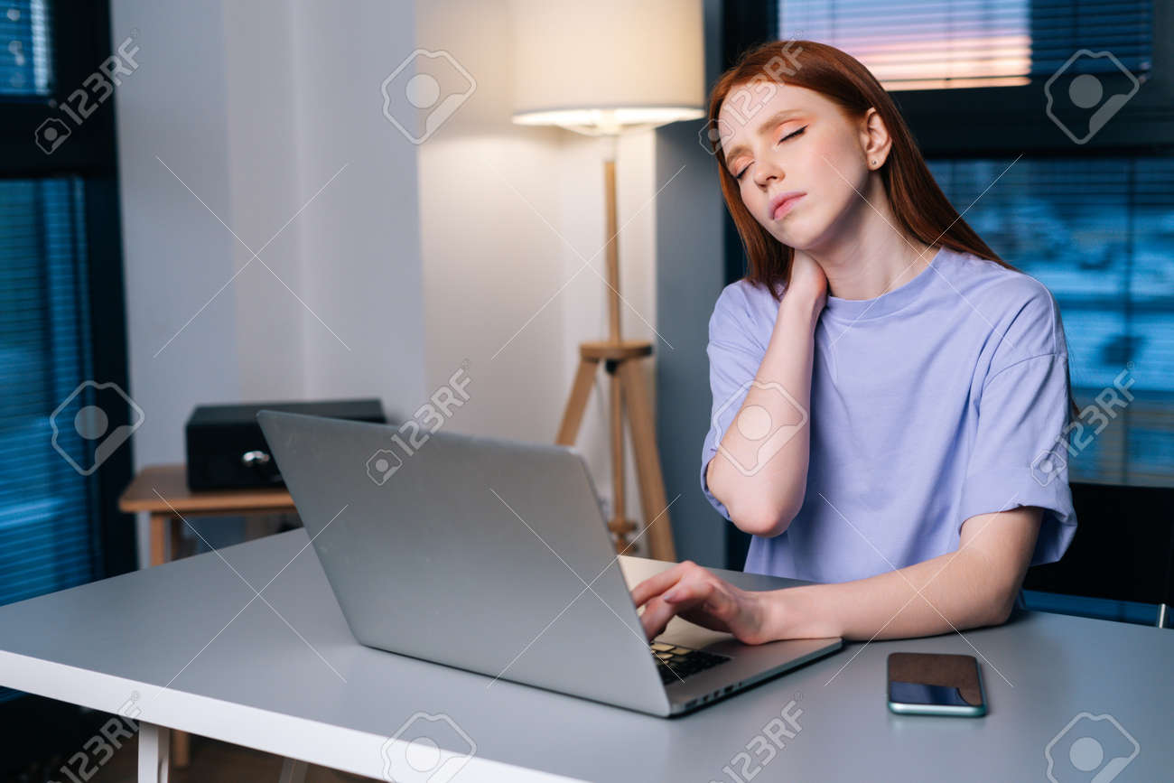 Overworked redhead young woman typing on laptop actively feeling pain in wrist sitting at desk near window in evening. Lady working on laptop and suffering from pain in hand, carpal tunnel syndrome. - 169892832