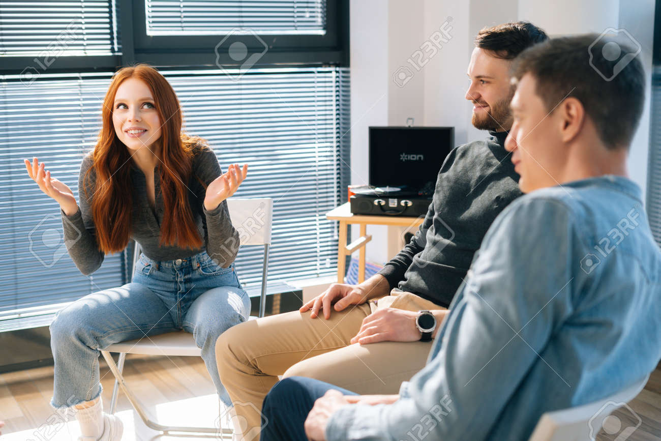 Middle shot portrait of cheerful young redhead businesswoman talking and discussing new ideas with creative business team, during brainstorming of start-up projects in modern office room near window. - 169892857