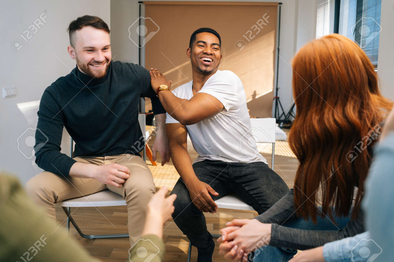 Laughing African American male leader explaining new strategies to young creative business team, during brainstorming in meeting room. Businessman discussing work with team in boardroom. - 169892863