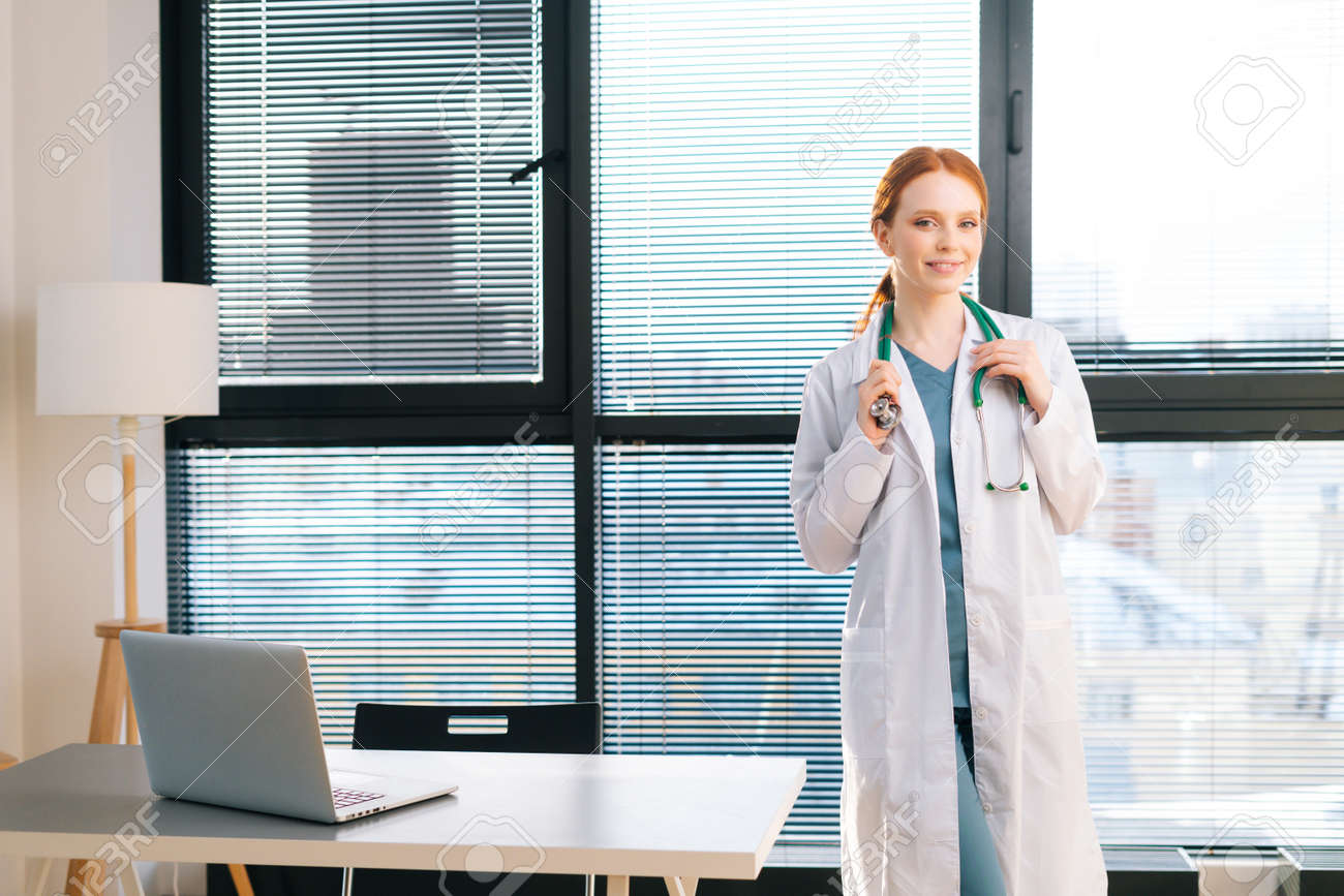 Portrait of pretty female doctor in white coat standing on background of window in sunny day in light medical clinic office. Young redhead woman physician posing with stethoscope looking at camera. - 169892865