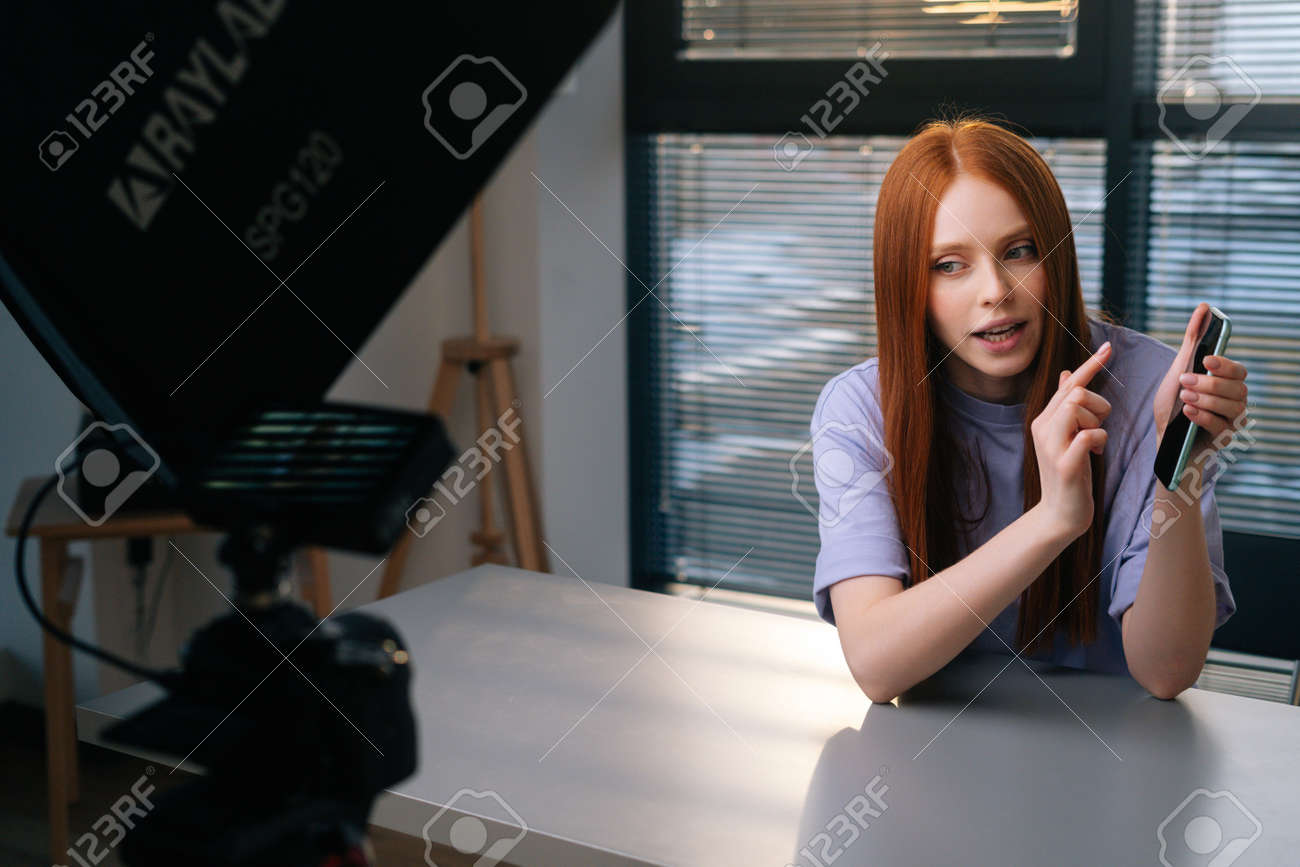 Webcam view of smiling young woman blogger greeting followers and talking about phone during video chat on background of window. POV of cheerful redhead female having presentation during sundown. - 169892872