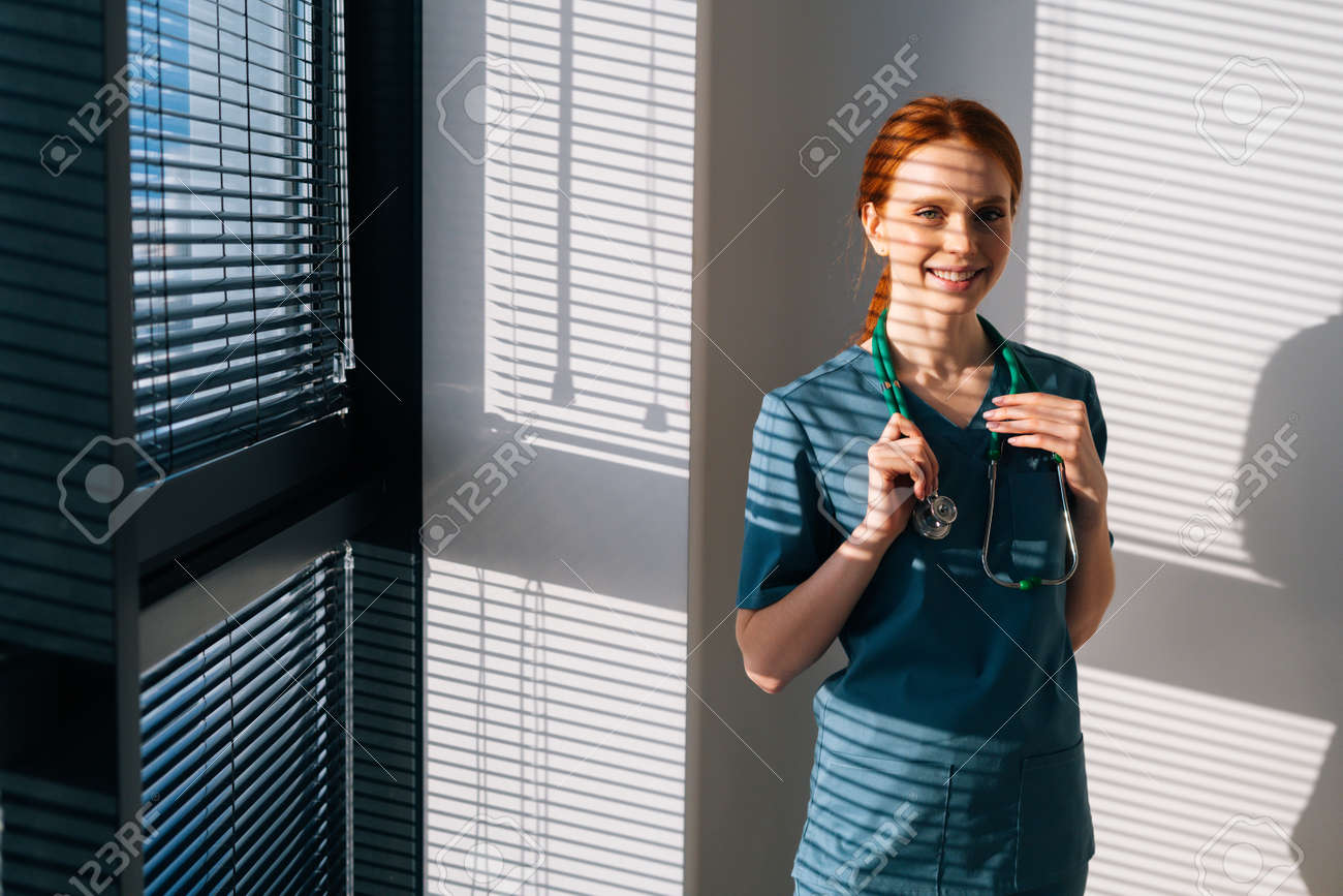 Portrait of positive female doctor in blue green uniform standing near window in sunny day in medical clinic office. Young pretty redhead woman surgeon posing with stethoscope looking at camera. - 169892885