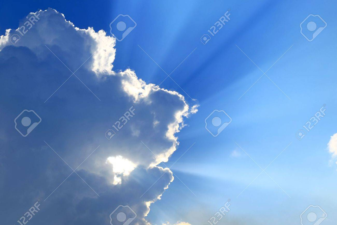 Rays of Sun beaming through clouds in the blue sky Stock Photo - 8009099